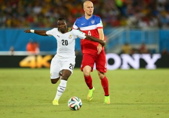 Ghana defensive midfielder Kwadwo Asamoah dribbling past U.S. attacking midfielder Michael Bradley.