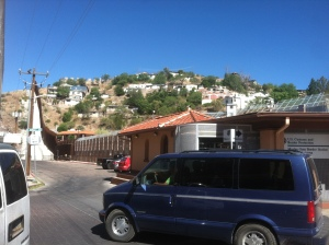 A van driving by the border wall separating Nogales, AZ from Nogales Sonora