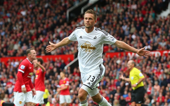 Sigurdsson celebrating with an agonized Rooney in the background.